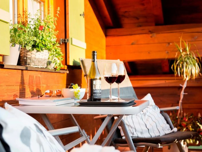 Gemütlich gedeckter Tisch im Abendlicht auf dem Balkon der Ferienwohnung Kaiserblick