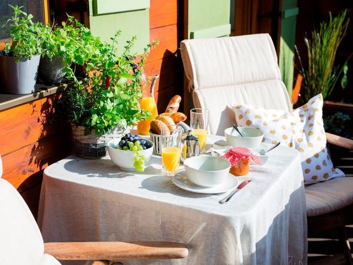 Blick auf den in der Sonne gedeckten Frühstückstisch der Ferienwohnung Waldidyll